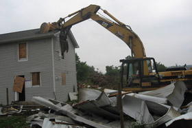 Photo of a excavator demolishing a house